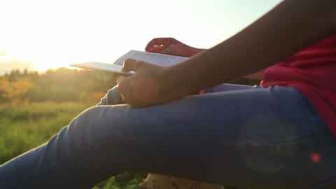 Young woman sitting in a park and reading a book Footage