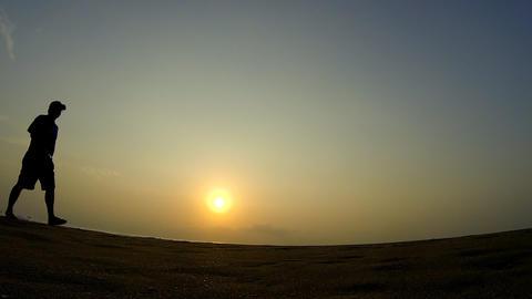 Silhouette of man walking along Footage