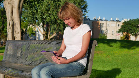 Attractive girl sitting on a bench in a park and using a tablet computer. Dolly Footage