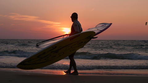 Man Carries Windsurfing After Riding The Waves stock footage