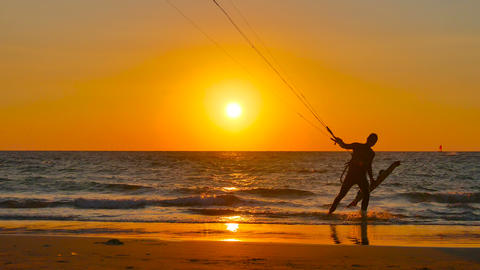 Kite Surfing Man Comes Out Of The Sea At Sunset stock footage