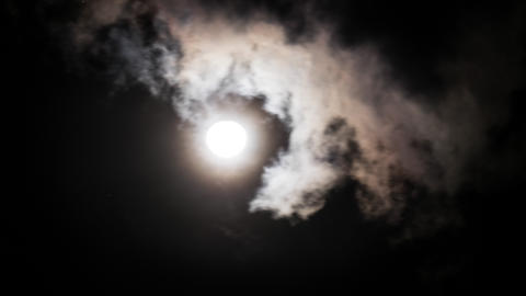 Amazing night sky with shining full moon behind moving dramatic clouds. Time lap Footage