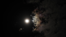 Night sky with shining full moon behind moving dramatic clouds. Time lapse Footage
