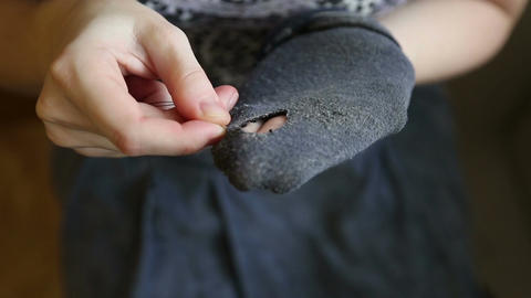 A woman sews up holes in socks Footage