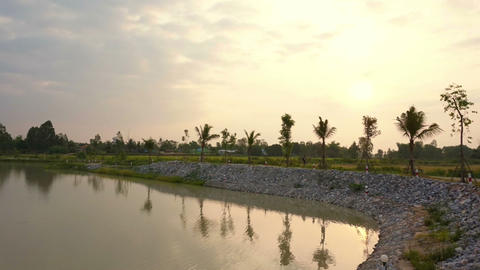 Sunrise At Lake, Man Made Water Reservoir With Rice Field And Palm Trees Backgro stock footage