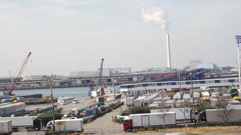 Pipe with white smoke in industrial area with lake and port in the front Footage