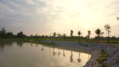Sunrise at lake, man made water reservoir with rice field and palm trees backgro Footage