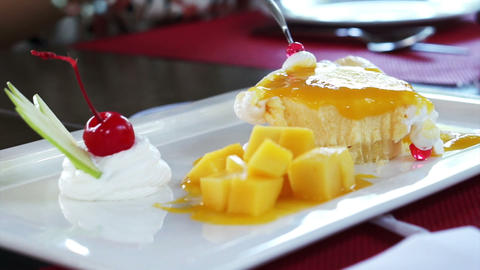 Eating Mango Cheese Cake on white plate with fresh fruit decoration Footage