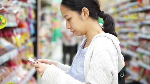 Asian girl, woman shopping snacks in supermarket Live Action