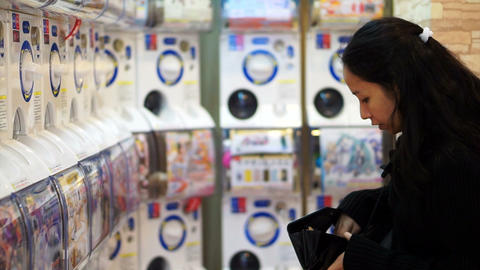 OSAKA, JAPAN - MARCH 2015: Girl looking for coins to play toy vending machine in Footage