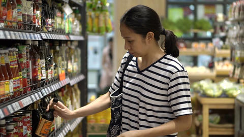 Asian girl, woman walking, looking and shopping in supermarket isle Footage