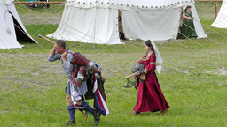 Medieval knight carries his armor. Slow motion. Medieval village in background Footage