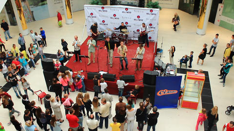 The band performs at the opening of the supermarket Live Action