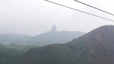 Big Buddha Monument Far In Hazy Air. As Seen From Moving Cable Car Gondola stock footage