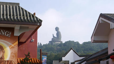 Pan from Buddha image on building wall to Big Budda statue far away on hill top Footage