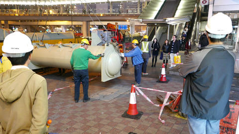 Workman group unloads steel cylinder heavy equipment on busy pedestrian street Footage