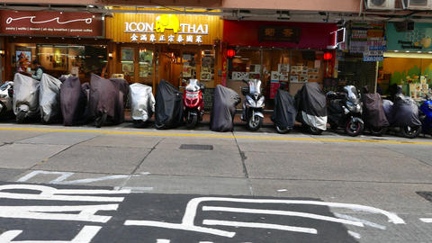Pan shot of scooters parked at street side, many vehicles stand in line Footage