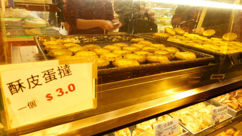 Egg tarts at bakery store showcase rack, night city scene, live camera Footage