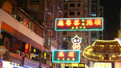 Neon advertising boards, signs above street in urban area, pan shot Footage