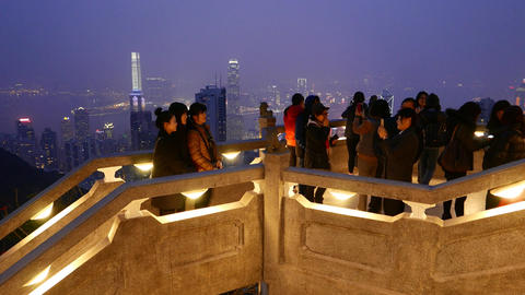 Tourists on Victoria Peak, against amazing night aerial skyline of Hong Kong Footage