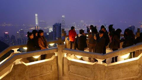 Tourists on Victoria Peak, against amazing night aerial... Stock Video Footage