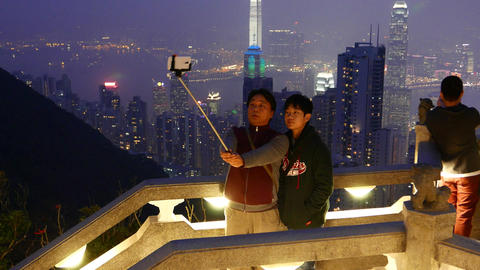 Father and son make selfie against amazing night Hong Kong cityscape Footage