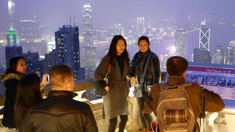 Two women photographed against night aerial city, open-air deck Footage