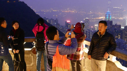 Asian tourists take pictures of amazing night panoramic city view Footage