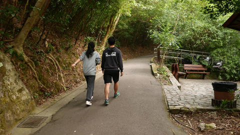 Following Young Asian Couple Rising Up Forest Track stock footage