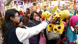 Chinese street market visitor buy fun soft toy, give... Stock Video Footage