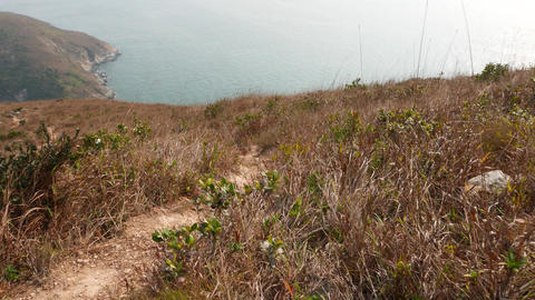 Climb down along trampled trail from island mountain to... Stock Video Footage