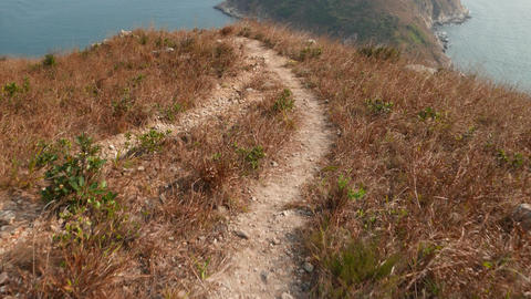 POV walk along rural hill trail, stone and dry grass,... Stock Video Footage