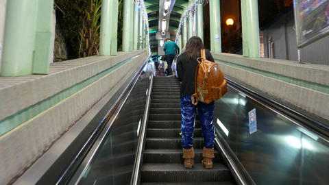 Standing still behind the woman with yellow backpack, on the escalator Footage