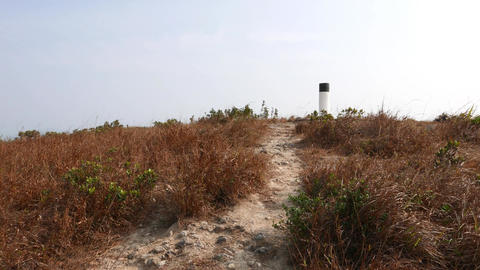 Walk over peak trail, pass geodesic column. Dry grass at... Stock Video Footage
