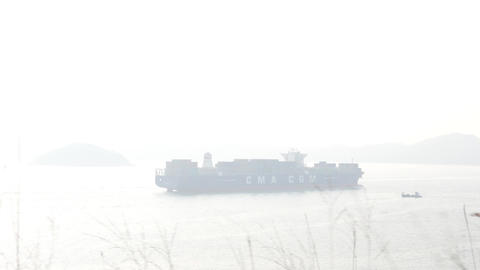 CMA CGM container ship in foggy sea, telephoto view from... Stock Video Footage