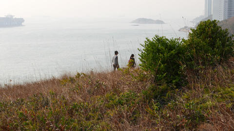 Small group hiking on top of hill, early evening, mountain sea landscape Footage
