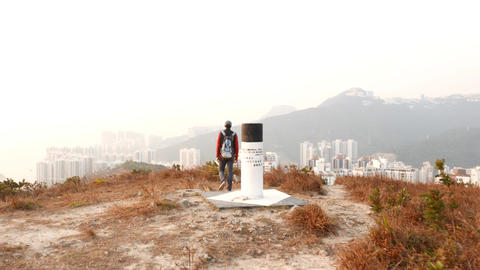 Hike over top point of mountain, look down to cityscape Footage