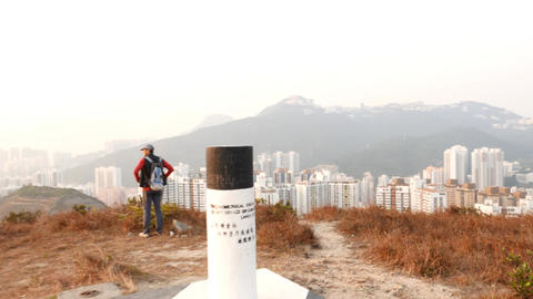 Hike over top point of mountain, look down to cityscape Stock Video Footage