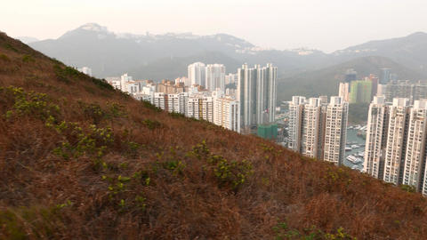Ap Lei Chau sleeping quarters behind dry grass hillside... Stock Video Footage