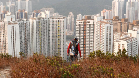 Hiker look down high hill edge, stand against massive dormitory blocks area Footage
