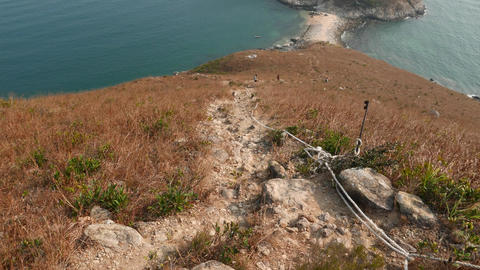Steep path lie downhill, sea shore and small island seen... Stock Video Footage