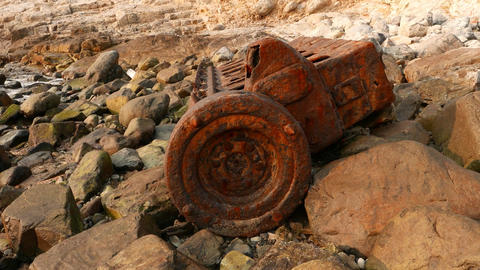 Vessel engine rusty carcass on rocky shore, POV camera approach to Footage