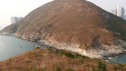 Pan shot island hill, aquamarine bay water and urban... Stock Video Footage