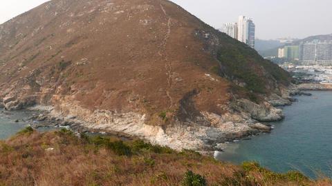 Pan Shot Island Hill, Aquamarine Bay Water And Urban Shore Far Away stock footage