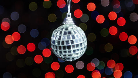 Mirror ball rotates at background of bokeh lights Stock Video Footage