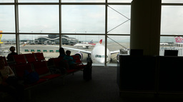 Waiting in airport gate lounge - passenger silhouettes, trucking shot Footage