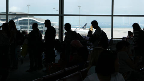 Black figures passengers queue departure gate against terminal window Footage