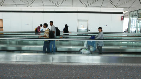People walk beside and along moving walkway in both directions, side view Live Action