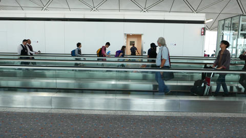 People walk beside and along moving walkway in both... Stock Video Footage
