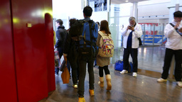 Young chinese couple walk through gangway door to airport arrival area Footage